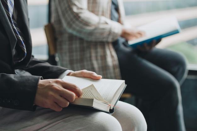 Le persone che leggono la sacra bibbia. due uomini che leggono un libro. insegnante e studente che leggono insieme. Foto Premium