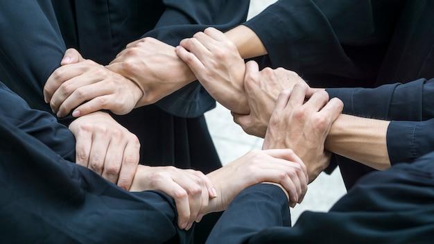 Le persone con abiti neri si uniscono a mano nel giro del cerchio Foto Premium