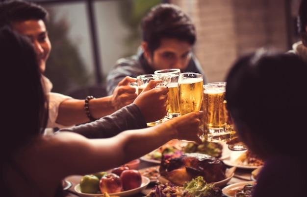 Le persone in asia stanno festeggiando il festival e tintinnano bicchieri di birra e cena felici Foto Premium