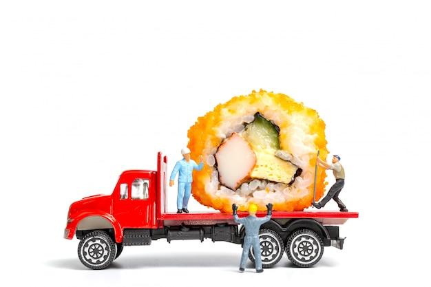 Le persone in miniatura fanno rotoli di sushi su camion, concetto di consegna del cibo Foto Premium