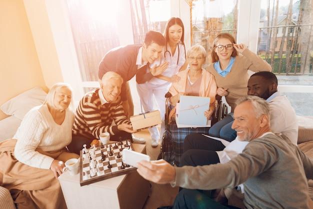 Le persone in una casa di cura fanno un selfie con una donna anziana Foto Premium