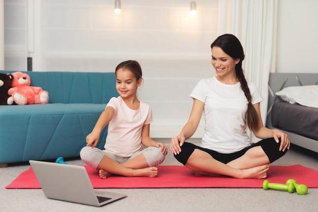 Le persone nella posizione del loto a casa guardano un portatile Foto Premium