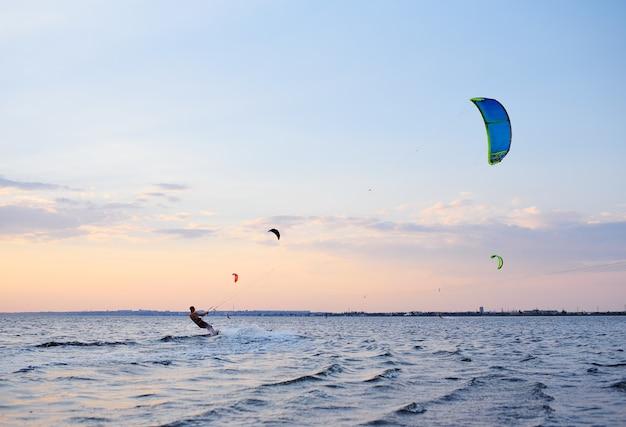 Le persone nuotano nel mare su un kiteboard o kitesurf Foto Premium