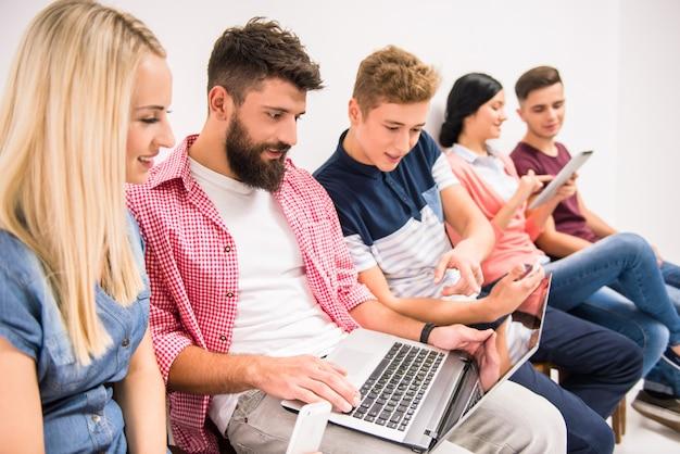 Le persone siedono in fila e fanno clic su un computer portatile. Foto Premium