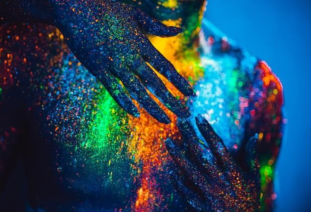 Le persone sono colorate in polvere fluorescente. una coppia di innamorati che balla in discoteca. Foto Premium
