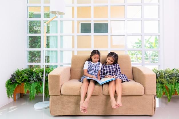 Le piccole ragazze dello studente godono di leggere il libro sul sofà a casa Foto Premium