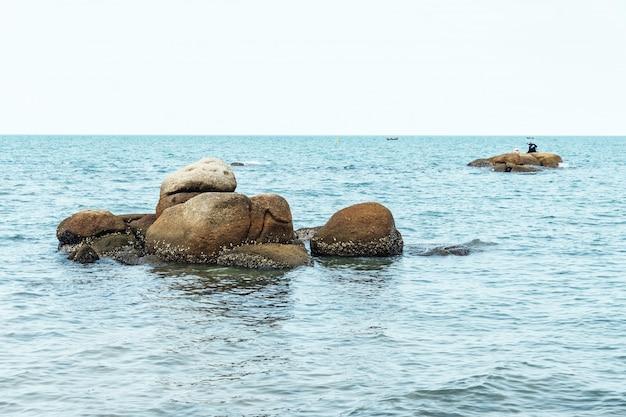 Le pietre del mare in mezzo al mare con il cielo luminoso sullo sfondo in chon buri, tailandia. Foto Premium