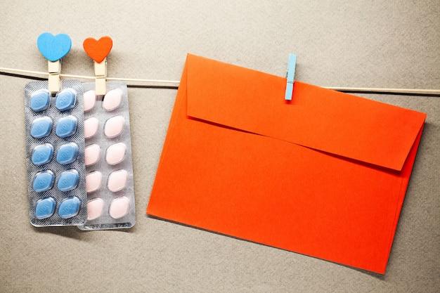 Le pillole e la busta maschii di salute appendono su una corda Foto Premium