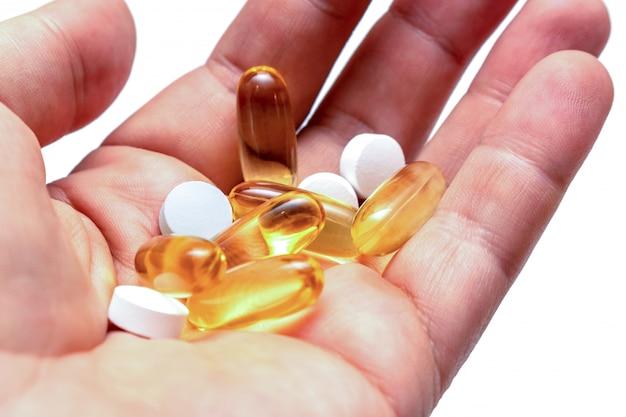 Le pillole gialle dell'olio di pesce della vitamina e omega 3 in vitamine di una mano mettono in mostra la nutrizione sana sulla fine isolata fondo bianco su Foto Premium
