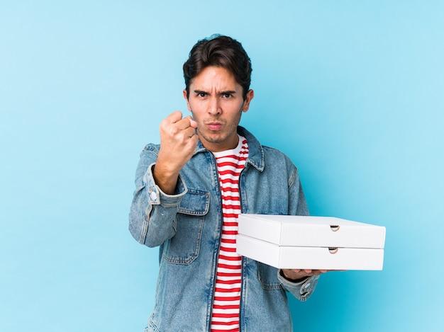 Le pizze caucasiche giovani della tenuta dell'uomo hanno isolato il pugno di mostra alla macchina fotografica, espressione facciale aggressiva. Foto Premium