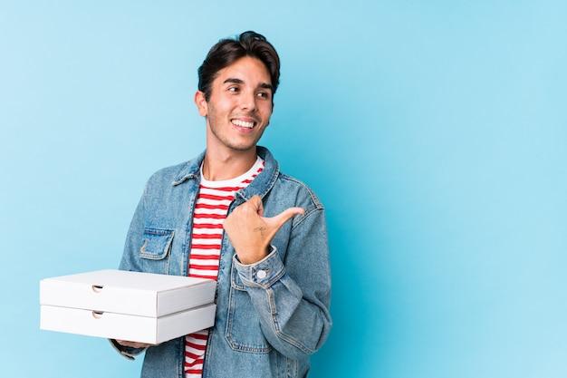 Le pizze della giovane tenuta caucasica dell'uomo hanno isolato i punti con il dito del pollice via, ridendo e spensierato. Foto Premium