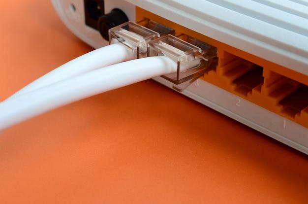 Le prese del cavo internet sono collegate al router internet, che si trova su uno sfondo arancione brillante Foto Premium