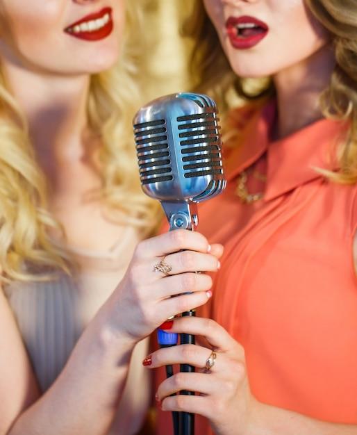 Le ragazze cantano karaoke nel ristorante. Foto Premium