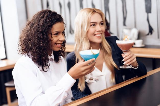 Le ragazze ordinarono cocktail, si siedono al banco del bar. Foto Premium