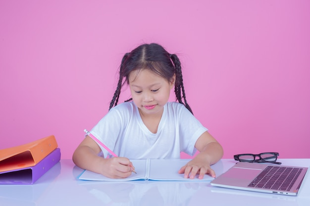 Le ragazze scrivono libri su uno sfondo rosa. Foto Gratuite