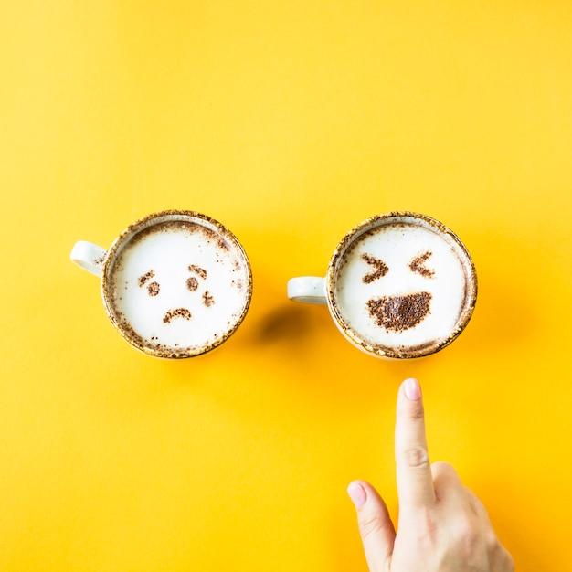 Le risate e la tristezza di emoji sono disegnate su tazze da cappuccino su uno sfondo giallo Foto Premium