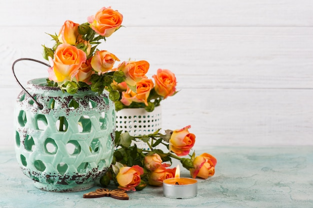 Le rose arancio fresche fiorisce in vaso della menta e candela accesa Foto Premium