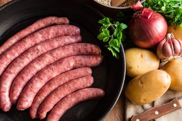 Le salsicce di maiale crude crude in ferro colano le erbe delle verdure della padella sulla cena del tavolo da cucina Foto Premium