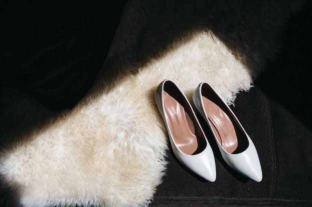 Le scarpe da sposa della sposa stanno su un sofà Foto Gratuite
