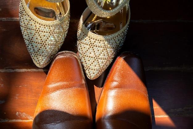 Le scarpe dello sposo di brown e le scarpe bianche della sposa dispongono sui precedenti di legno Foto Premium