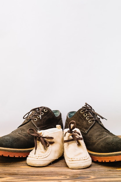 Le scarpe maschii si avvicinano agli stivali del bambino sul bordo di legno Foto Gratuite