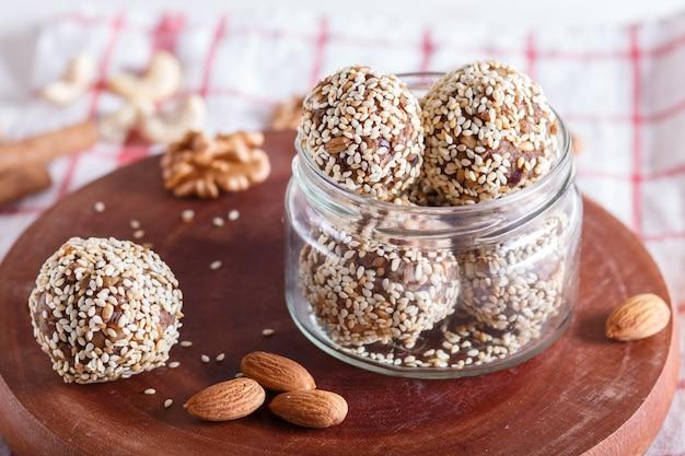 Le sfere di energia agglutina con le date delle noci dell'anacardio del sesamo delle mandorle e il grano germinato nella fine di vetro del barattolo su Foto Premium