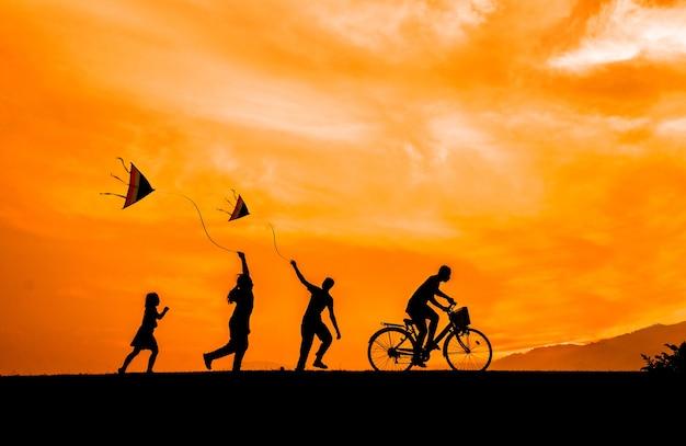 Le siluette dei bambini giocano con gli aquiloni ed i ciclisti al tramonto. Foto Premium