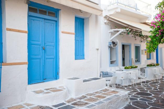 Le stradine dell'isola con balconi blu, scale e fiori. splendida architettura esterna dell'edificio in stile cicladico. Foto Premium