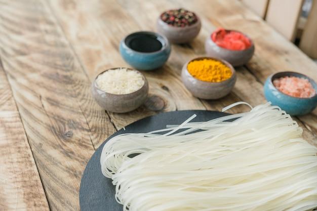 Le tagliatelle di riso crude bianche fresche sopra l'ardesia oscillano con le spezie sulla tavola di legno Foto Gratuite