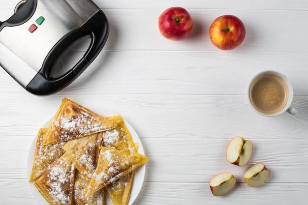 Le torte si trovano sul tavolo accanto alle mele, un tostapane e una tazza di caffè Foto Premium
