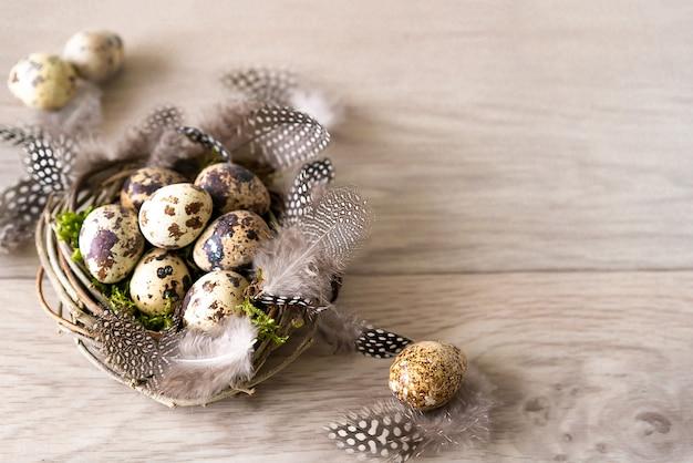 Le uova di pasqua e la piuma delle quaglie in uccello annidano su fondo di legno rustico Foto Premium