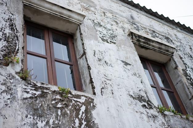 Le vecchie finestre marroni e di legno si trovano sul muro dell'antica casa. Foto Premium