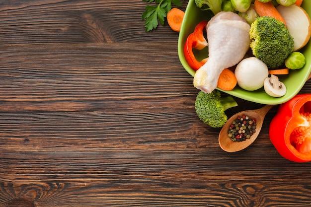 Le verdure di vista superiore si mescolano e coscia di pollo in ciotola e cucchiaio di legno con lo spazio della copia Foto Gratuite