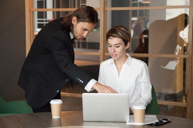 Leader maschile che aiuta il partner a collaborare con l'avvio online Foto Gratuite