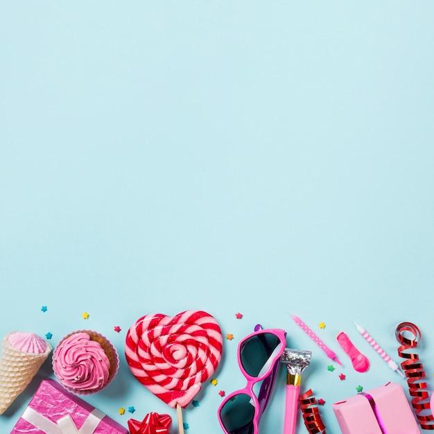 Lecca-lecca a forma di cuore; muffin; cono; pacco regalo; palloncino; candela; streamer e scatole regalo sullo sfondo blu Foto Gratuite