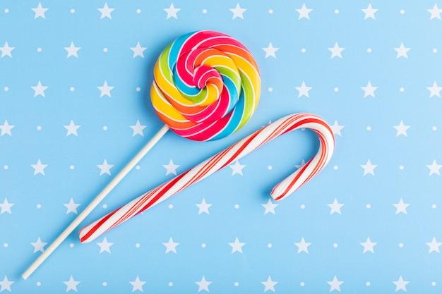Lecca-lecca multicolore rotonda e cono di caramella isolati su un blu con il fondo delle stelle. natale, inverno, anno nuovo o concetto di compleanno. Foto Premium