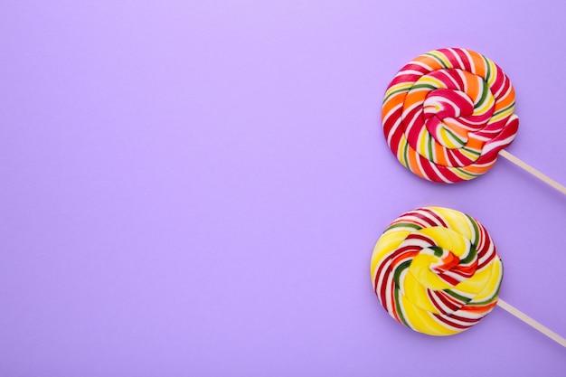 Lecca-lecca variopinte sulla tavola porpora, concetto della caramella dei dolci Foto Premium