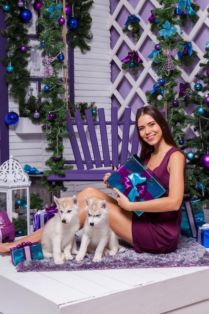 Leggy bruna in un abito bordeaux seduto su un tappeto viola Foto Premium