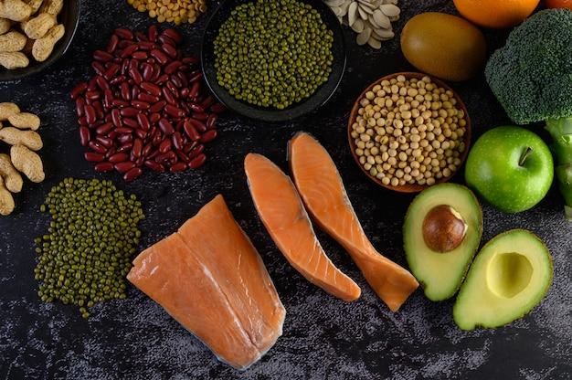 Legumi, broccoli, frutta e salmone posti su un pavimento di cemento nero. Foto Gratuite