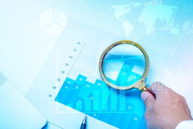 Lente d'ingrandimento e documenti con dati analitici che si trovano sul tavolo, finanza aziendale Foto Premium