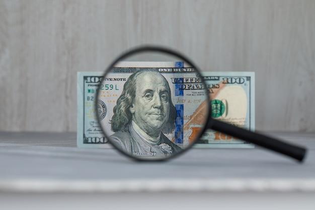 Lente d'ingrandimento sopra la banconota del dollaro sul tavolo grigio e in legno Foto Gratuite