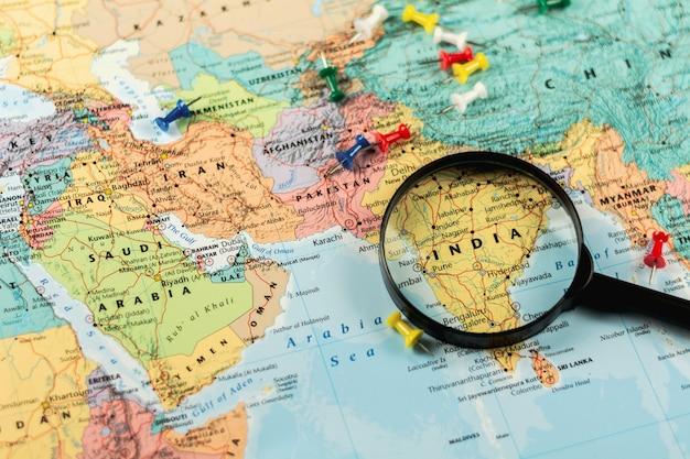 Lente d'ingrandimento sulla mappa del mondo messa a fuoco selettiva in india. - concetto economico e di business. Foto Premium