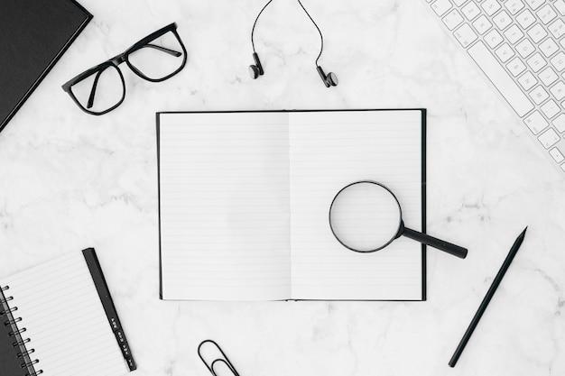 Lenti d'ingrandimento sul notebook circondate da tastiera; occhiali; auricolare; matita; e diario su sfondo strutturato Foto Gratuite
