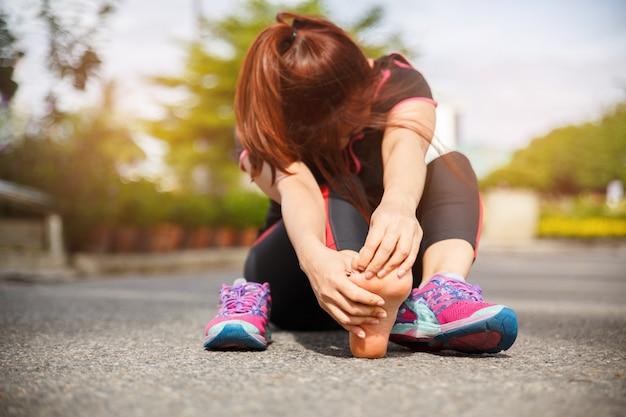 Lesione e dolore del piede dell'atleta del corridore femminile. donna che soffre di doloroso piede durante l'esecuzione su strada. Foto Premium