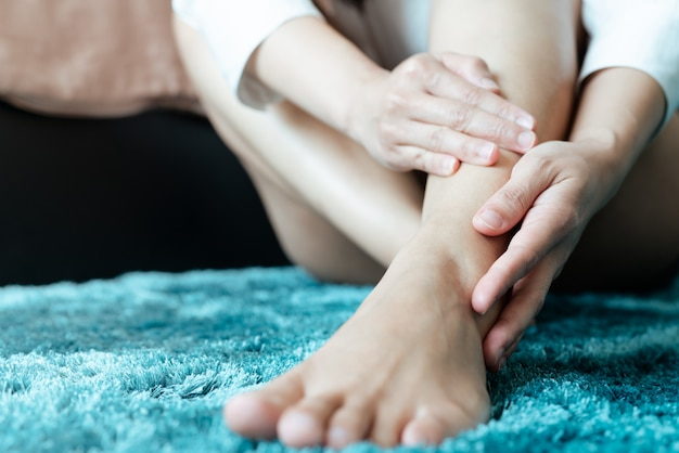 Lesioni alle caviglie alle gambe delle donne / dolorose, le donne toccano il dolore alla gamba della caviglia Foto Premium