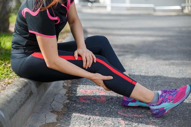 Lesioni e dolore della gamba dell'atleta del corridore delle donne. donne che soffrono di gambe doloranti mentre corrono sulla strada. Foto Premium