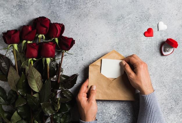 Lettera di amore della busta della tenuta della mano dell'uomo di giorno di biglietti di s. valentino con la cartolina d'auguri Foto Gratuite