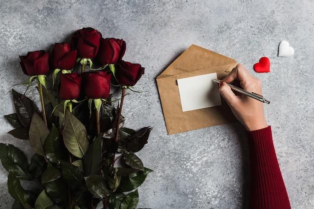 Lettera di amore di scrittura della penna di tenuta della mano della donna di giorno di biglietti di s. valentino con la cartolina d'auguri Foto Gratuite