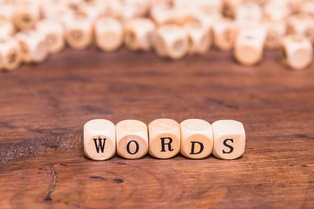 Lettera di parole fatta con cubetti di legno su scrivania marrone Foto Gratuite