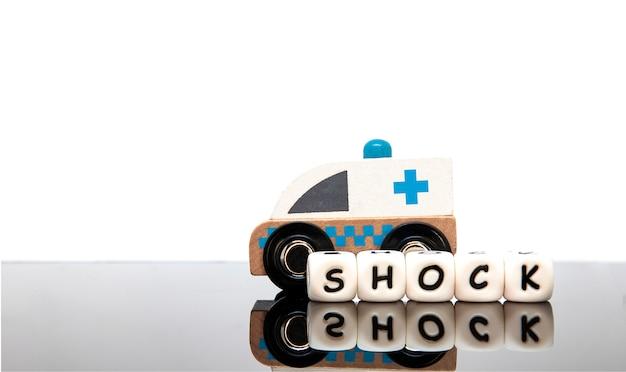 Lettere di alfabeto che compitano lo shock di parola e un'ambulanza giocattolo Foto Premium